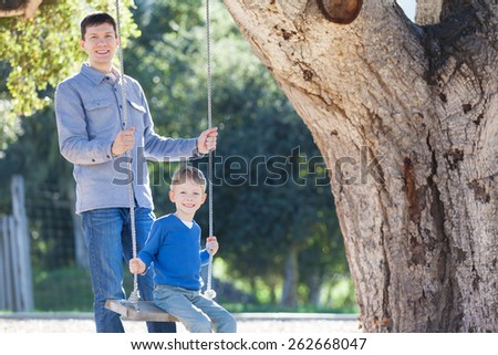 handsome young father and his little son enjoying time together and having fun in the park swinging - stock photo