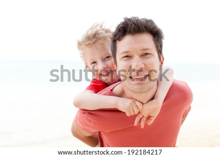 handsome young father and his little son hugging together at the beach, tropical vacation - stock photo