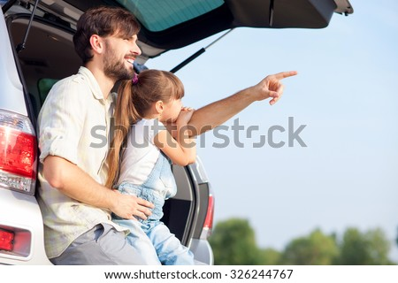 Handsome young father and his small daughter are sitting on open car boot in forest. The parent is pointing finger sideways and smiling. Girl is looking there with interest. Copy space in right side - stock photo