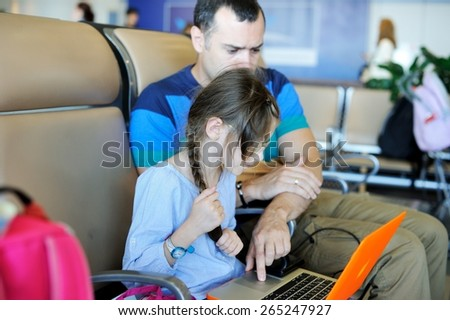 Handsome young father  and little daughter using laptop at airport - stock photo