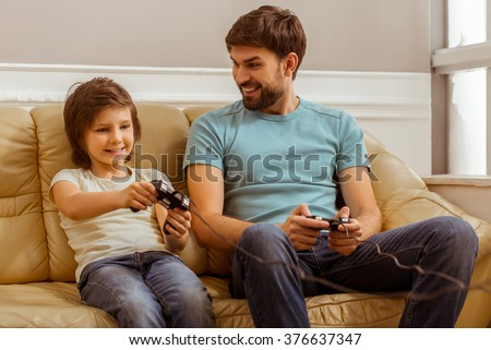 Handsome young father in casual clothes and his cute little son playing console games and laughing while sitting on a sofa in the room - stock photo