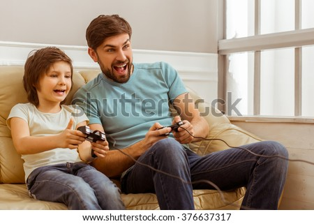 Handsome young father in casual clothes and his cute little son playing console games while sitting on a sofa in the room - stock photo