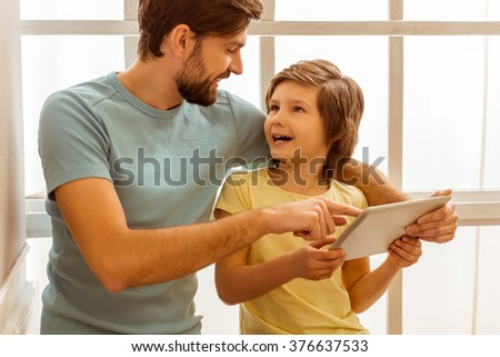 Handsome young father in casual clothes and his cute little son using a tablet and smiling while sitting near the window - stock photo