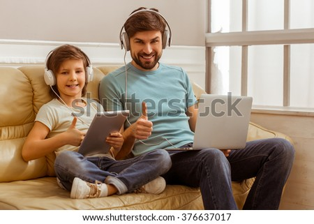 Handsome young father in casual clothes using a laptop and his cute little son using a tablet while sitting on a sofa in the room. Both in headphones showing OK sign, looking in camera and smiling. - stock photo
