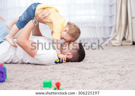 Handsome young father is playing with his sun. He is lying on flooring and holding the child under him with joy. They are smiling. Copy space in right side - stock photo