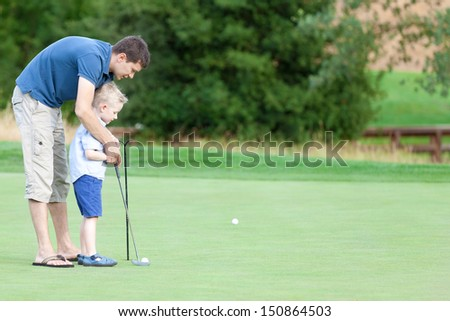 handsome young father teaching his cute son to play golf - stock photo