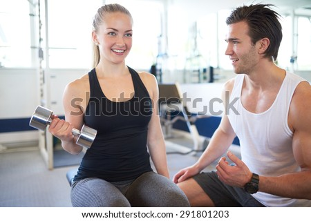 Handsome Young Fitness Trainer Assisting a Pretty Female in Lifting Weights Inside the Gym - stock photo