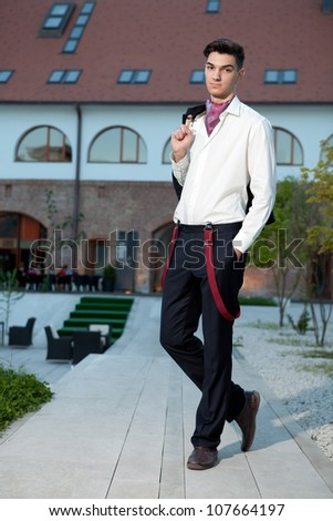 Handsome young hipster fashion male model wearing shirt and red braces posing outdoors - stock photo