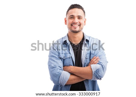 Handsome young Hispanic guy smiling with his arms crossed against a white background - stock photo
