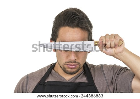 handsome young male chef wearing black apron holding knife in front of eyes isolated on white - stock photo