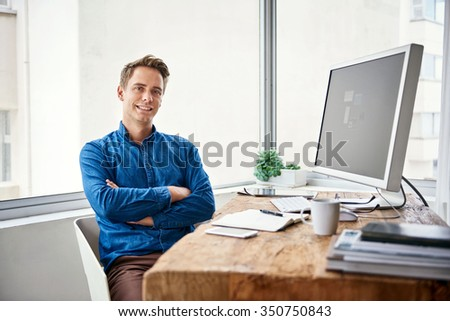 Handsome young male entrepreneur sitting confidently at his desk in a contemporary office space with large windows - stock photo