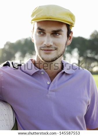 Handsome young male golfer on golf course - stock photo