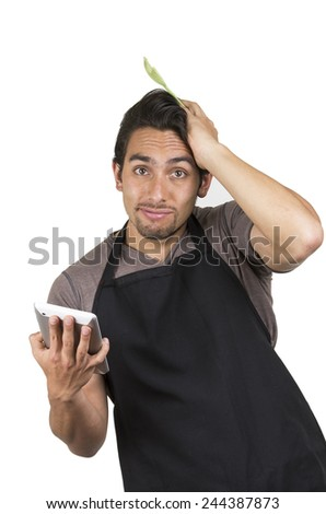 handsome young male rookie chef wearing black apron holding a tablet looking lost isolated on white - stock photo
