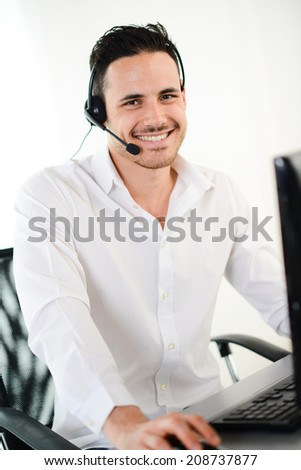 handsome young male telephone customer support hotline service talking on the phone with client - stock photo
