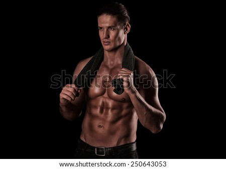 handsome young man after a workout with a towel around his neck - stock photo
