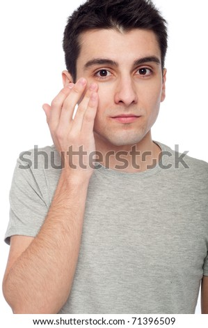 handsome young man applying eye cream for dark circles (isolated on white background) - stock photo