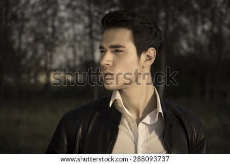 Handsome young man at countryside at night or late evening, in field or grassland, wearing white shirt and jacket, looking away to a side - stock photo