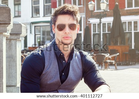 Handsome young man. Attractive guy in summer or spring wearing sunglasses. - stock photo