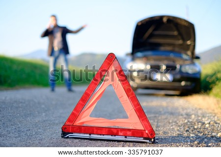 Handsome young man calling for assistance with his car broken down by the roadside - stock photo