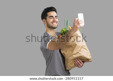 Handsome young man carrying a bag full of vegetables and making a selfie, isolated over gray background - stock photo