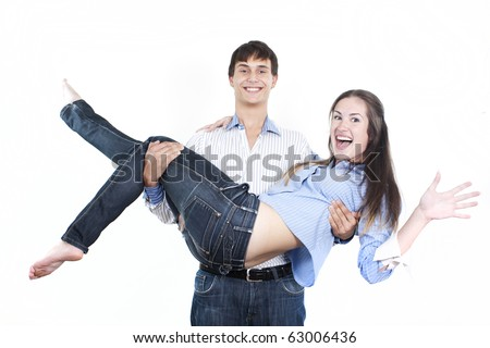 Handsome young man carrying cute girlfriend in his arms - stock photo