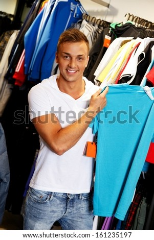 Handsome young man choosing t-shirt in a sport outlet - stock photo