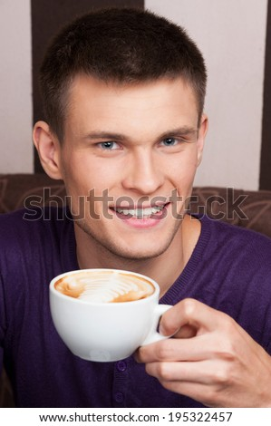handsome young man close up picture. man drinking coffee in coffee shop - stock photo