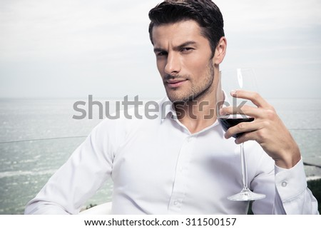Handsome young man drinking wine outdoors - stock photo