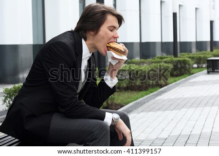 Handsome young man eat his delicious cheeseburger at the office building - stock photo