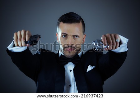 Handsome young man gangster police spy agent assissin holding and pointing with two guns wearing a suit - stock photo