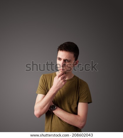 Handsome young man gesturing with empty space - stock photo