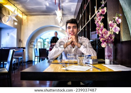 Handsome young man having lunch in elegant restaurant alone smiling and looking at camera - stock photo
