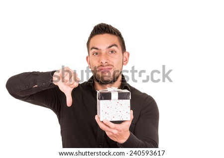 handsome young man holding a gift box with thumb down isolated on white - stock photo