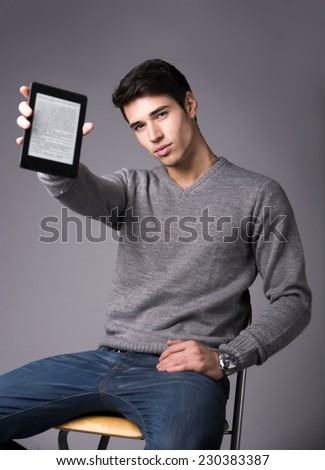Handsome young man holding and showing ebook reader and looking at camera, sitting on grey background - stock photo