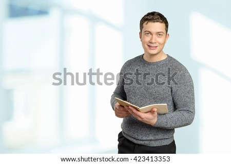Handsome young man holding book - stock photo