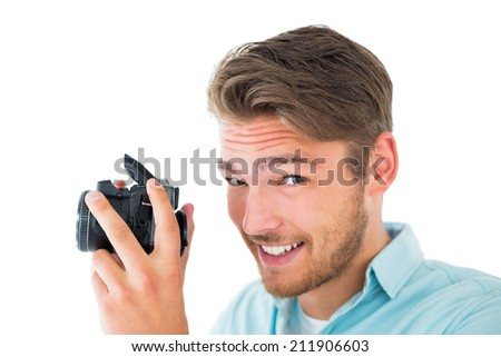 Handsome young man holding digital camera on white background - stock photo