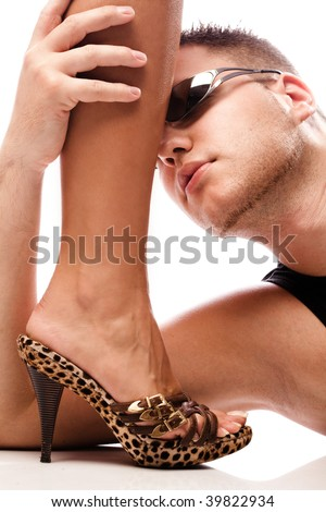 handsome young man holding female leg in high heels, studio white - stock photo