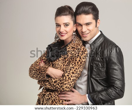 Handsome young man holding his lover while she is holding her arms crossed, both smiling for the camera. - stock photo