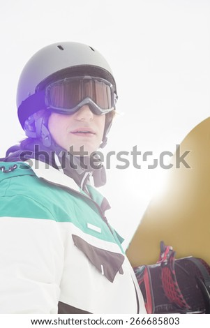 Handsome young man holding snowboard outdoors - stock photo