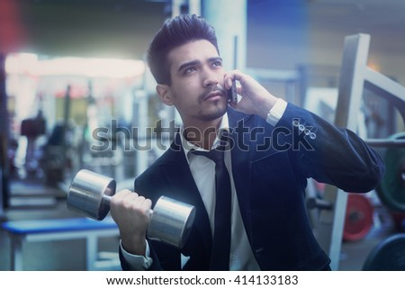 Handsome young man in a black suit, white shirt and tie talking on the phone with a dumbbell in hand in the gym - stock photo