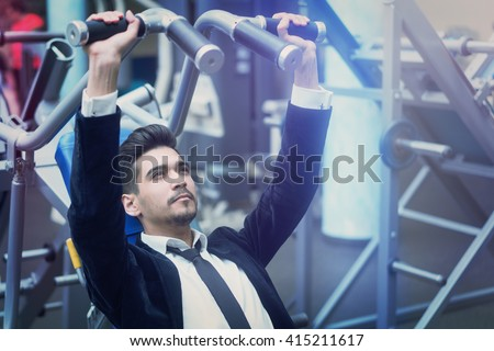Handsome young man in a black suit, white shirt and tie training in the gym - stock photo