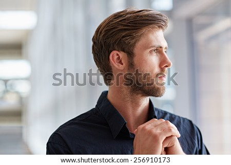Handsome young man in a formal shirt looking seriously out into the distance - stock photo
