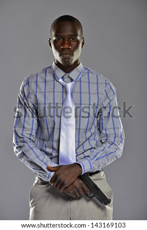 Handsome young man in a shirt and tie holding a firearm at his waist ready to go. - stock photo