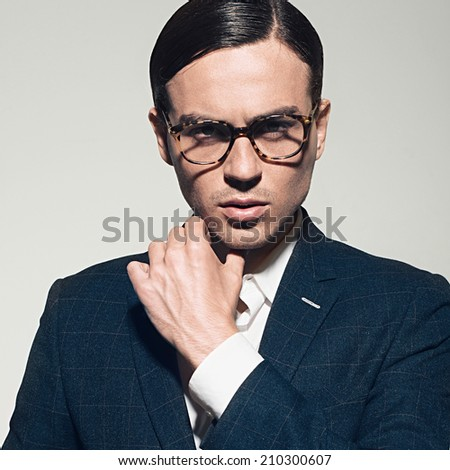 Handsome young man in a suit and fashionable glasses, posing in studio - stock photo