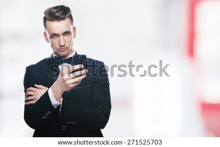Handsome young man in a tuxedo looking at the camera. Fashionable Clothing. Clothing for the festive evening. Elegant man calling on the phone - stock photo