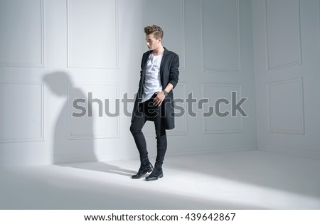 Handsome young man in an empty room - stock photo