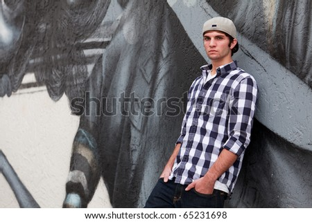 Handsome young man in an urban fashion lifestyle pose leaning on a graffiti wall wearing a baseball cap. - stock photo