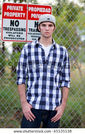 Handsome young man in an urban lifestyle fashion pose along a fenced lined sidewalk. - stock photo