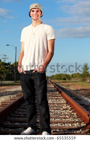Handsome young man in an urban lifestyle fashion pose standing on a railroad track. - stock photo