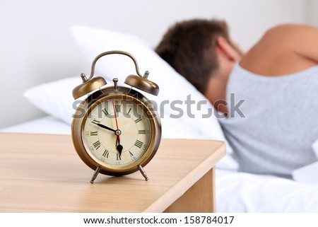 Handsome young man in bed - stock photo